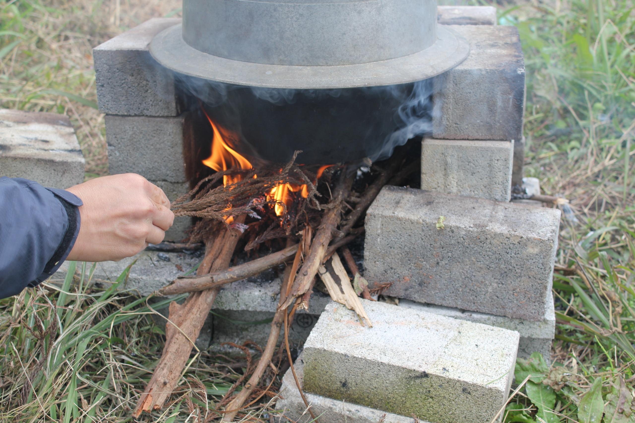 火を起こし、釜で炊いている様子